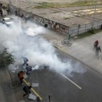 People, amidst tear gas, run away from police oficcers during looting in Concepcion, Chile, Sunday, Feb. 28, 2010. A 8.8-magnitude earthquake hit Chile early Saturday. (AP Photo/Aliosha Marquez)