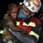 A small child in Haiti is rescued by a rescue party member.